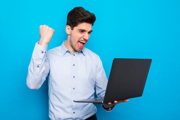 Emotional young man with laptop celebrating victory isolated on blue space