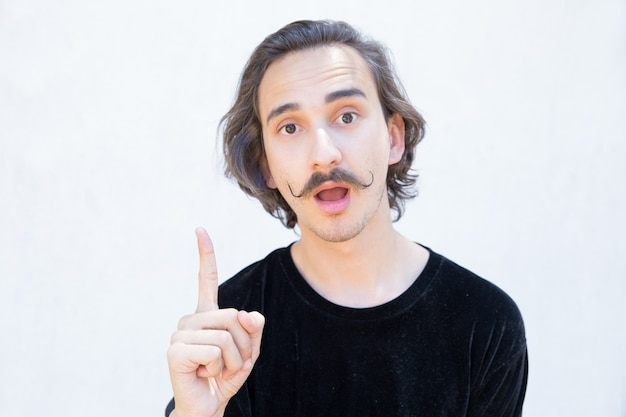 Emotional young man with mustache pointing up with finger