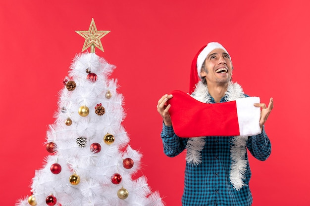 Emotional young man with santa claus hat in a blue stripped shirt and holding christmas sock looking above
