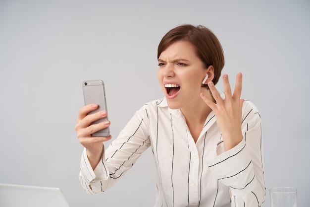 흰색에 포즈를 취하는 동안 휴대 전화를 들고 스트레스가 많은 화상 통화에 화가 나서 외치는 동안 그녀의 얼굴을 찌푸린 캐주얼 헤어 스타일로 감정적 인 젊은 꽤 짧은 머리 갈색 머리 여성