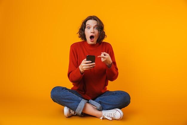 Эмоциональная молодая красивая женщина позирует изолированной на желтой стене с помощью мобильного телефона.