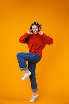 Emotional young pretty woman posing isolated on yellow wall listening music with headphones dancing.
