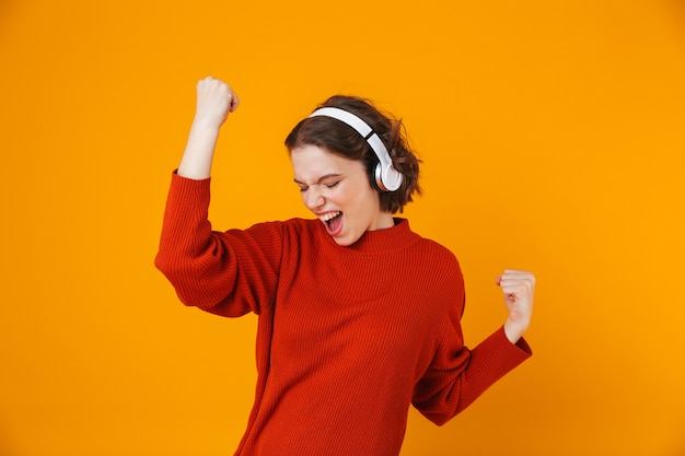 Emotional young pretty woman posing isolated on yellow wall listening music with headphones make winner gesture.