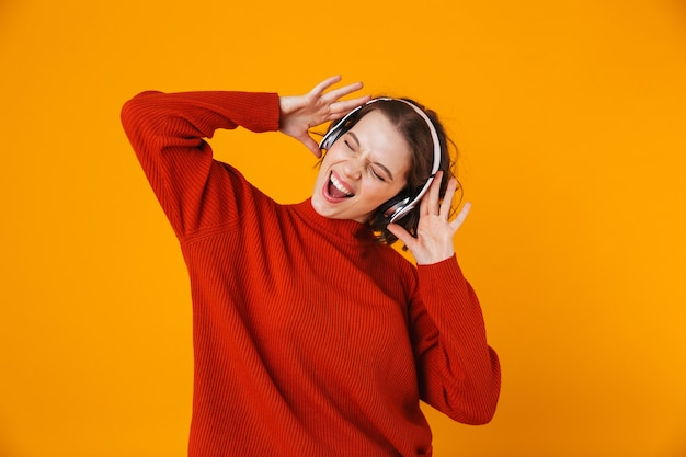 Emotional young pretty woman posing isolated on yellow wall listening music with headphones.