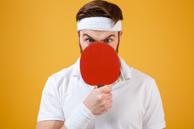 Emotional young sportsman holding racket for tennis covering mouth.