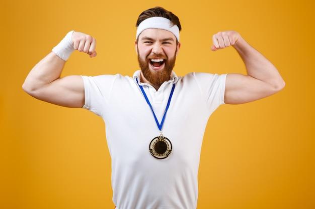 彼の上腕二頭筋を示すメダルと感情的な若いスポーツマン