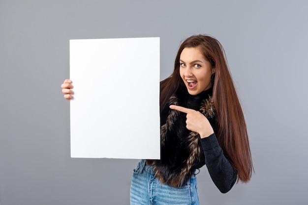 灰色で隔離のコピースペースと空白の看板を示す感情的な若い10代の女性