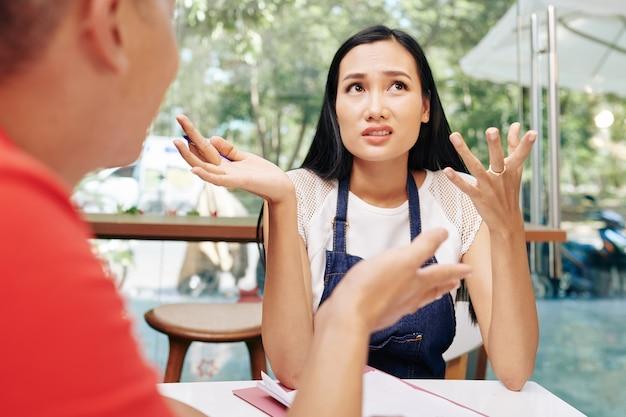 야외 테이블에 앉아있을 때 비즈니스 파트너와의 문제를 논의하는 감정적 인 젊은 베트남 카페 주인