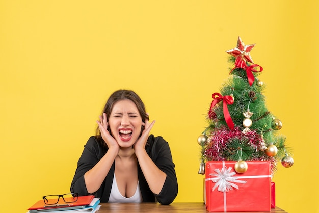 黄色のオフィスで飾られたクリスマスツリーの近くのテーブルに座って耳を閉じる感情的な若い女性