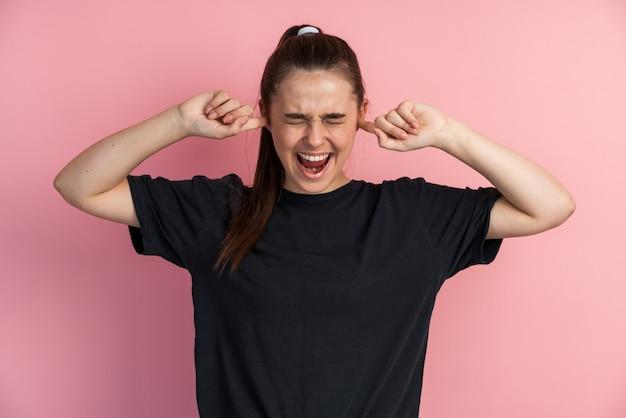 Эмоциональная молодая женщина закрыла уши пальцами