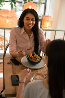 カフェで食事をし、向かいの友達と話しながら身振りで示す感情的な若い女性