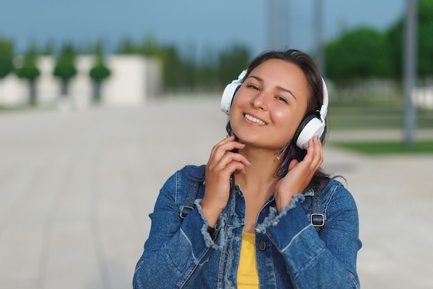 Emotional young woman in headphones listening music outdoors Premium Photo