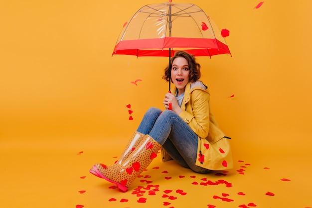 紙のハートで覆われている床に座っている黄色のゴム靴の感情的な若い女性。かわいい傘でポーズをとるインスピレーションを得た巻き毛の女の子の屋内写真。