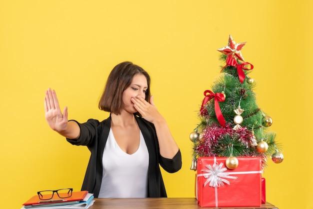 노란색에 사무실에서 장식 된 크리스마스 트리 근처 테이블에 앉아 정지 제스처를 만드는 감정적 인 젊은 여자