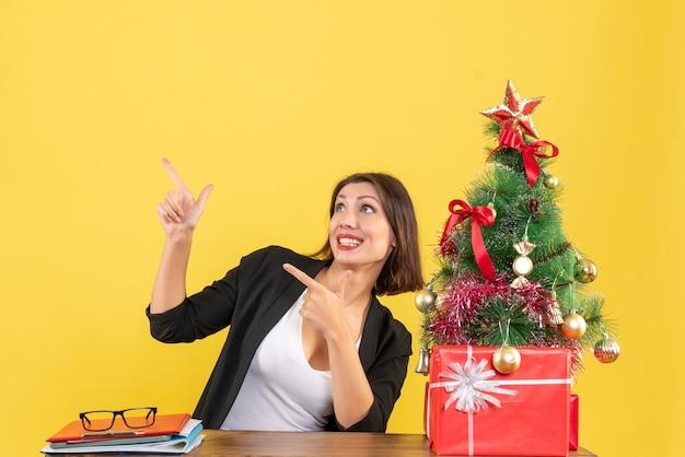 黄色のオフィスで飾られたクリスマスツリーの近くのテーブルに座って何かを指している感情的な若い女性