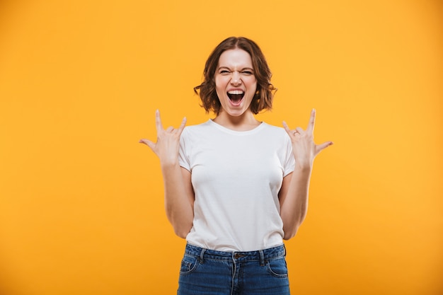 Emotional young woman showing rock gesture looking camera.