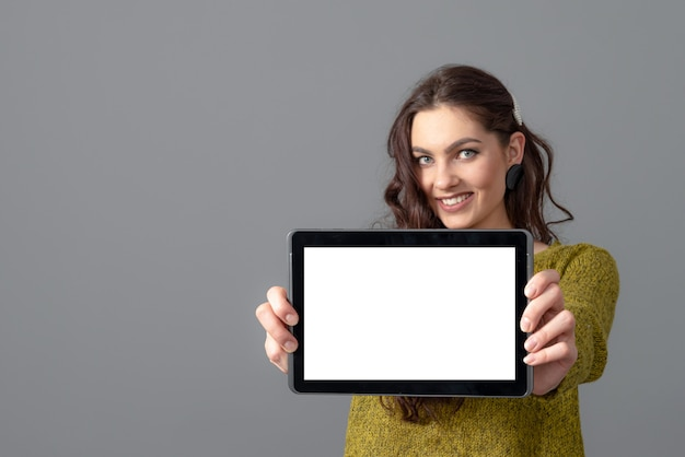 Emotional young woman showing tablet computer with empty touch screen on gray