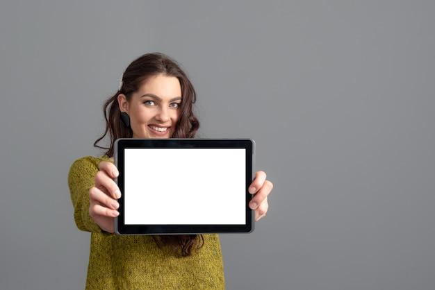 회색 배경에 고립 된 복사 공간을 가진 빈 터치 스크린 태블릿 컴퓨터를 보여주는 감정적 인 젊은 여자