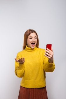 Emotional young woman using smartphone