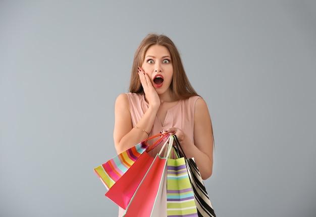 色の背景に買い物袋を持つ感情的な若い女性
