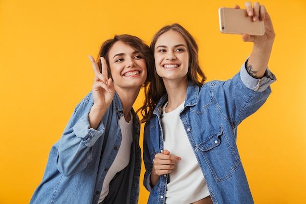 黄色い壁に隔離された感情的な若い女性の友人は、携帯電話で自分撮りをします。