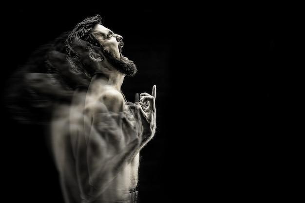 Эмоционально выразительная фотография кричащего бородатого мужчины, сердитый крик боли черно-белое фото.