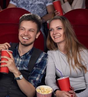 Эмоционально счастливая пара молодой и красивой девушки с длинными волосами и парня в клетчатой рубашке смотрит новый комедийный фильм в современном кинотеатре