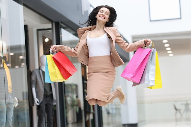 Emotionally happy woman jumping with shopping bags in mall