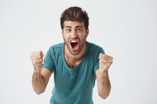 Emotions and achievement concept. close up shot of happy successful casually weared student or employee screaming with winning expression, fists pumped, celebrating success on a white wall