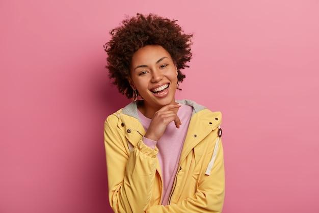 感情と顔の表情の概念。巻き毛の髪型の陽気な明るい女性は、あごの下に手を保ち、喜びで見て、楽しいニュースを聞きます