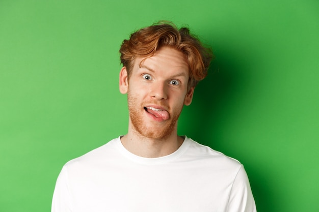 Эмоции и концепция моды. крупным планом смешной рыжий мужчина показывает глупые лица, высунув язык и смотрит в камеру, стоя на зеленом фоне