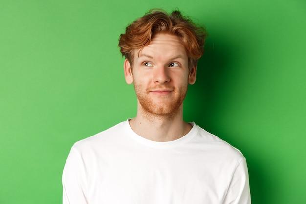 감정과 패션 개념. 수염과 지저분한 머리, 왼쪽보고 웃 고, 녹색 배경으로 잘 생긴 빨간 머리 남성 모델의 클로즈업.