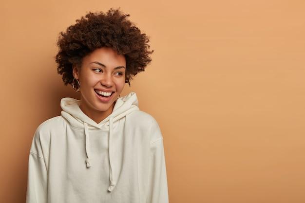 감정과 라이프 스타일 개념. 행복하게 기쁘게 생각하는 어두운 피부의 곱슬 머리 여자는 흰색 셔츠를 입고 웃고 재미 있고 옆으로 보입니다.