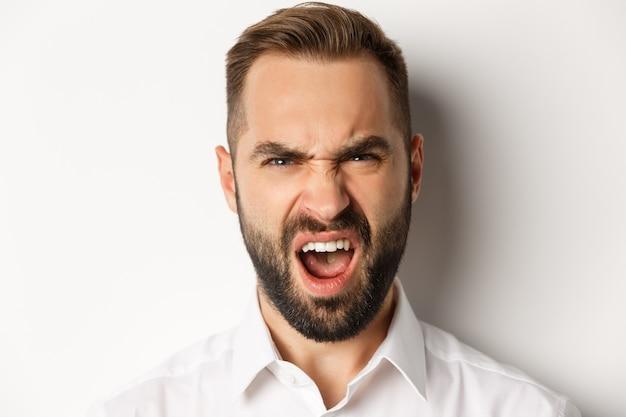 감정과 사람들 개념. 실망, 불평 및 찡그린 무언가에 반응하는 충격을받은 수염 난 남자의 근접
