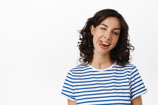 감정과 사람 개념입니다. 혀를 보여주는 행복한 브루네트 소녀, 윙크하고 웃고 행복하고 긍정적인 태도와 즐거운 감정을 흰색 위에 서 있습니다.