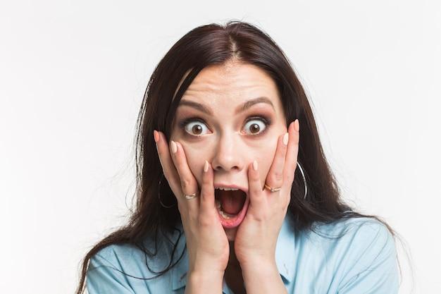 감정과 사람들 개념-젊은 여자가 놀란, 무서워하고 흰 벽에 손으로 그녀의 입을 닫습니다.