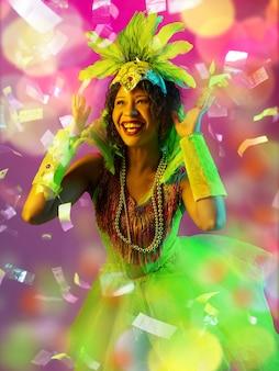 感情。カーニバルの美しい若い女性、ネオン、空飛ぶ紙吹雪のグラデーションの背景に羽を持つスタイリッシュな仮面舞踏会の衣装。休日のお祝い、ダンス、ファッション。お祝いの時間、パーティー。