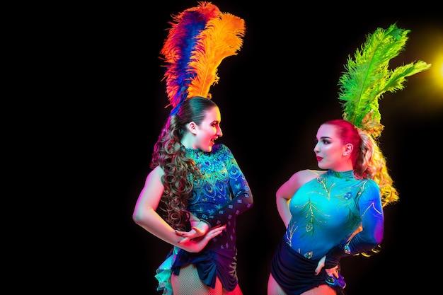 감정. 카니발, 네온 불빛에 검은 바탕에 깃털을 가진 세련 된 무도회 의상에서 아름 다운 젊은 여성. 광고 copyspace입니다. 휴일 축하, 춤, 패션. 축제 시간, 파티.