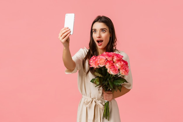 Emotions, beauty and romance concept. attractive excited, alluring brunette female holding beautiful roses, received flowers and taking selfie with amazed surprised expression, pink wall