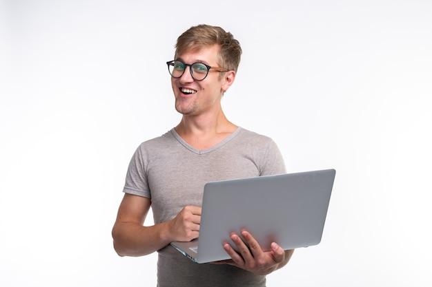 感情、教育、人々の概念。ラップトップを見て笑っている若いハンサムな男。