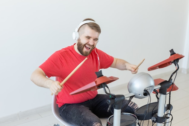 感情、電子ドラム、人々のコンセプト-ドラムを演奏する若い男性ドラマー。