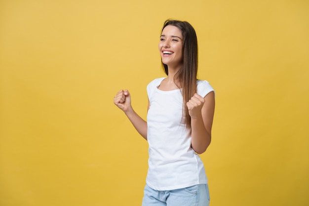 Emotions, expressions, success and people concept - happy young woman or teenage girl celebrating victory isolated over yellow background.