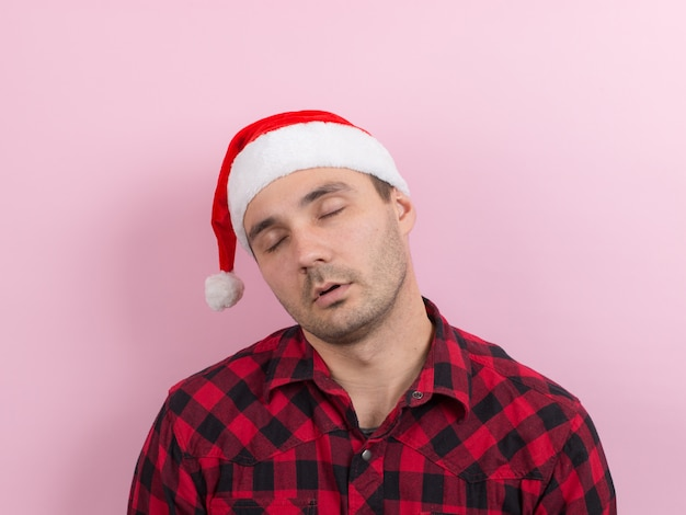 Emotions on the face, tired, holiday hangover, awareness. a man in a plaid rabbit and a christmas red hat