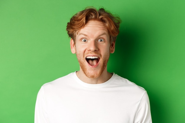 Emotions and fashion concept. close up of surprised redhead man hear amazing news, staring at camera joyful, standing over green background.