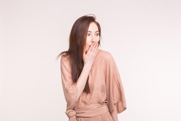 感情、感情、人々の概念。若い女性はショックを受けたので彼女の手で彼女の口を覆います。
