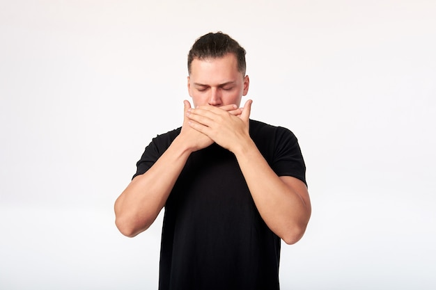 Emotions and feelings. portrait of scared man with closed eyes covering his mouth with hands