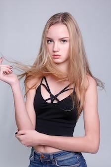 감정, 건강, 사람, 음식, 아름다움 개념 - 뷰티 모델 소녀는 쥬시 오렌지를 먹습니다. 주근깨, 재미있는 헤어스타일을 가진 아름다운 즐거운 십대 소녀. 노란색 메이크업. 전문 메이크업. 오렌지 슬라이스