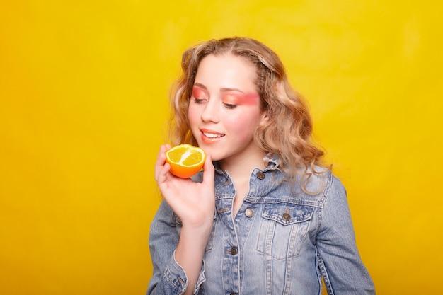 感情、健康、人、食べ物、美容のコンセプト – ビューティー モデル ガールはジューシー オレンジを採用そばかすのあるうれしそうな美しい十代の少女、面白い髪型。黄色いメイク。プロのメイク。オレンジスライス