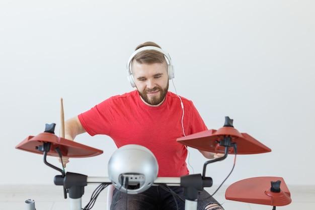 感情、趣味、音楽、人々のコンセプト-感情的なドラマーが電子ドラムを演奏します。