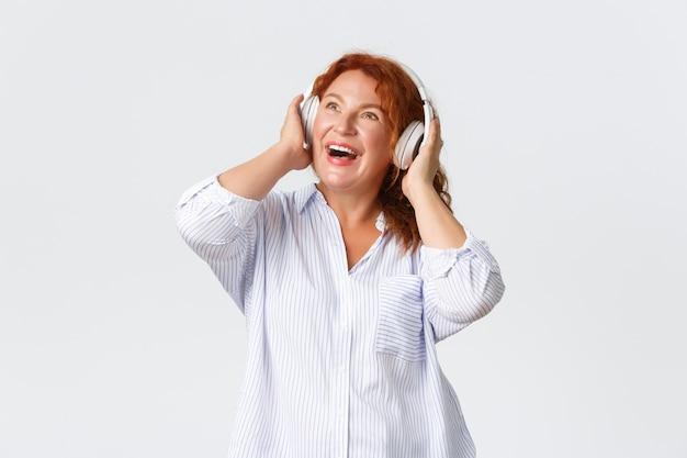 感情、ライフスタイル、レジャーのコンセプト。印象的で満足のいく赤毛の中年女性が、白い壁越しに陽気なヘッドホンのすごい音に驚きました。